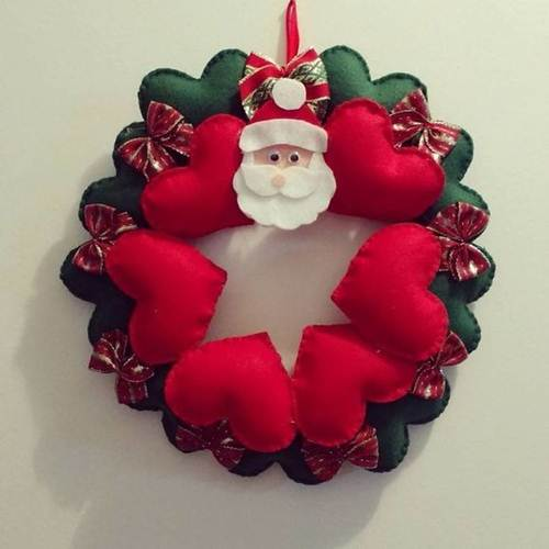 48f53d8e1a695 A guirlanda de feltro com corações verdes e vermelhos foi decorada com o  rosto do Papai Noel.